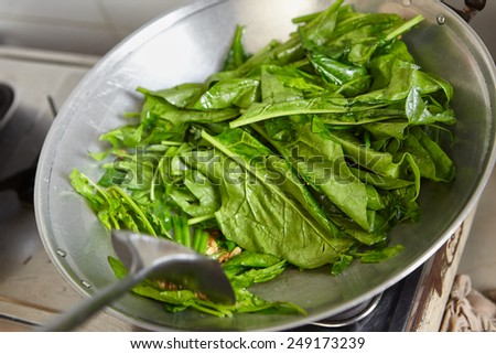 Sauteing or stir frying the japanese spinach in chinese style