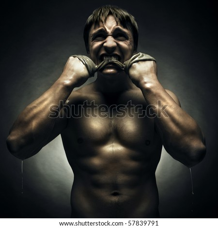 Savage athlete with a rag in his mouth - stock photo