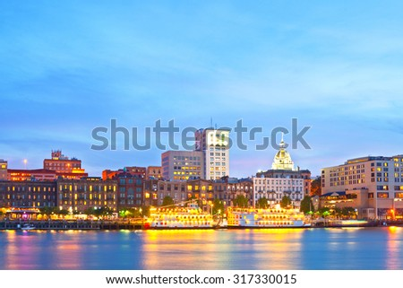 Savannah Georgia USA, skyline of historic downtown at sunset with illuminated buildings and steam boats - stock photo