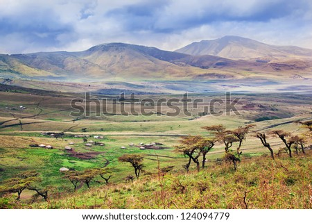 Savannah landscape in Tanzania, Africa. Maasai houses in the valley