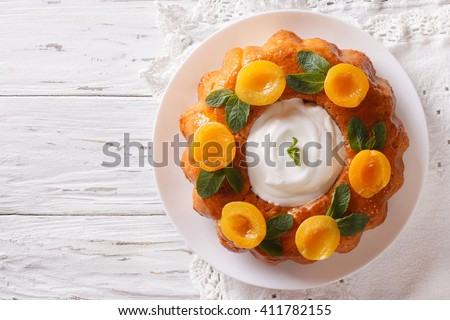 Savarin French dessert with apricots and whipped cream. vertical view from above