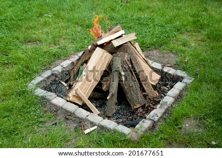 Save bonfire on green grass - stock photo