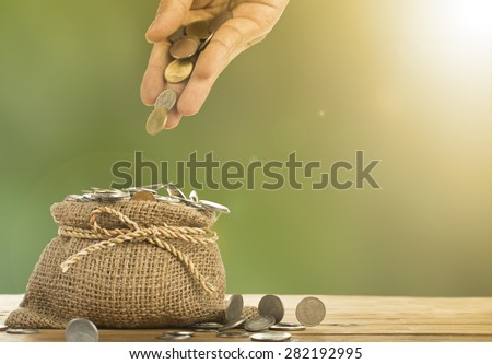 Save money concept with put money coin to bag in the morning. - stock photo