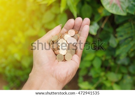 Save money for prepare in the future, Save money concept, Hand of young man with coins on blurred background