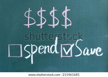 save money not spend written on blackboard - stock photo