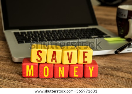 Save Money written on a wooden cube in a office desk - stock photo