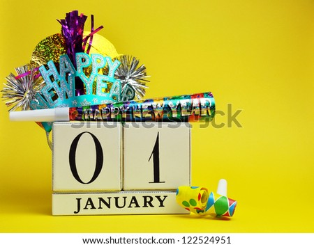 Save the date, January 1, with this decorative vintage white block calendar with Happy New Year hat and decorations against a bright and cheerful yellow background. - stock photo