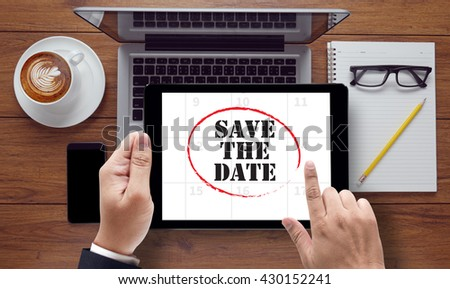 SAVE THE DATE , on the tablet pc screen held by businessman hands - online, top view - stock photo