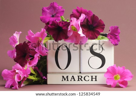 Save the date white block calendar for International Women's Day, March 8, decorated with pink and purple flowers against a pink purple background. - stock photo