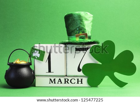 Save the date white block calendar for St Patrick's Day, March 17, with Leprechaun hat and pot of gold, on green background. - stock photo