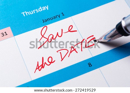 Save the date words written on calendar using pen - stock photo