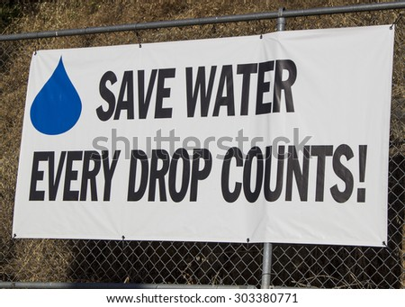 Save water, every drop counts signage on side of fence. - stock photo