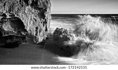 Saves break on a limestone outcropping on a Florida beach - stock photo