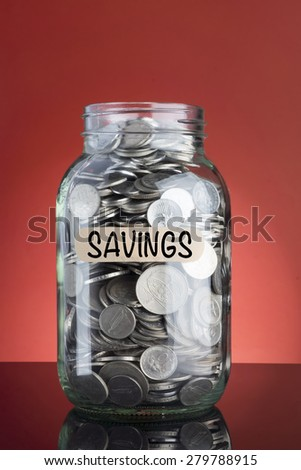 Saving Concept: Coins in money jar and Savings Text on red background