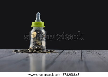 Saving Concept- coins in the baby milk bottle on wooden background - stock photo
