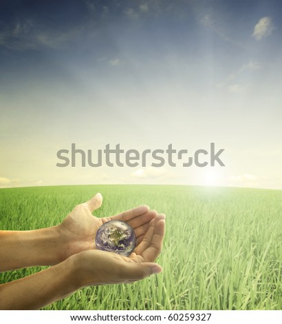 saving earth concept photo with hands holding a globe during a beautiful morning sunrise