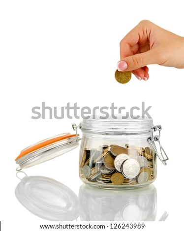 Saving, female hand putting a coin into glass bottle, isolated on white - stock photo