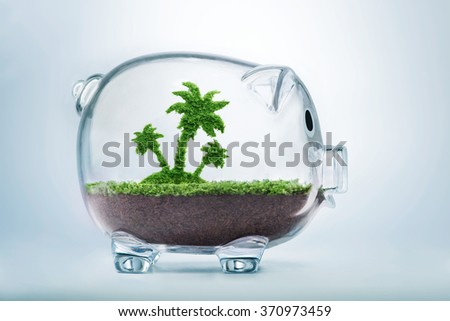 Saving for vacation concept with grass growing in shape of a palm tree inside transparent piggy bank - stock photo