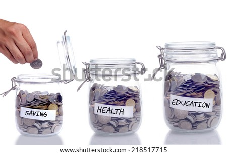 Saving, Health and Education concept: Glass jar with coin and hand putting the coin into the jar - stock photo
