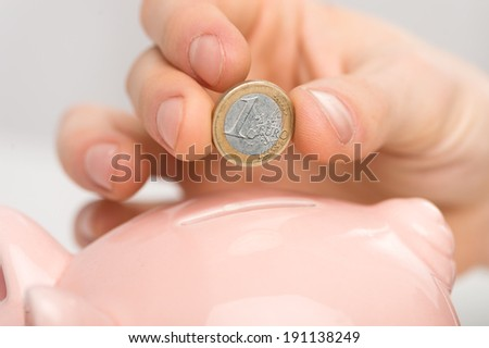 Saving. Male hand putting a coin into piggy bank - stock photo