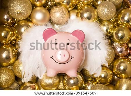 Saving money at christmas piggybank on gold baubles - stock photo
