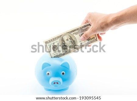 Saving money, by hand put dollar into piggy bank.
