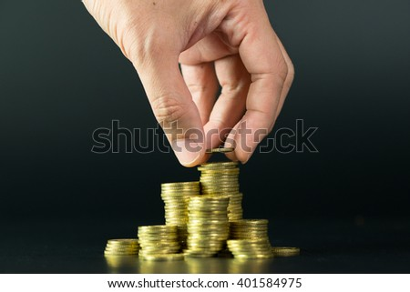 Saving money concept by adding a gold coin to a pile of coins