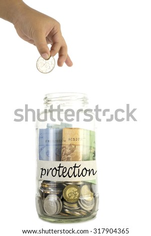 Saving money concept. Kid hand putting a coin into a glass jar with tagging 'protection' on masking tape isolated on white background.