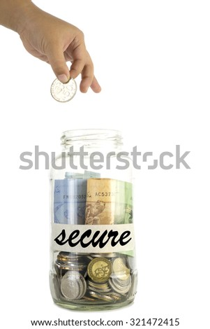 Saving money concept. Kid hand putting a coin into a glass jar with tagging 'secure' on masking tape isolated on white background.