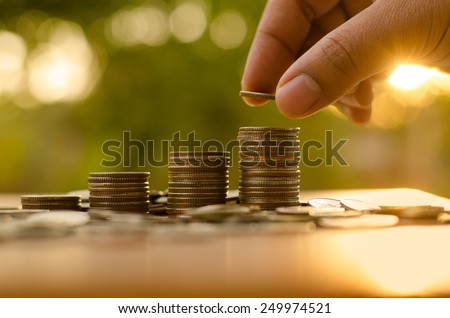Saving money concept,Male hand putting money coin stack growing business - stock photo