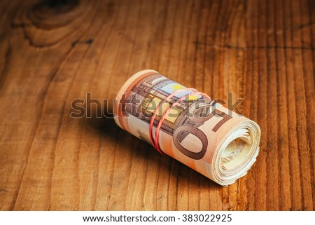 Saving money concept, rolled up cash money with rubber band on wooden desk, fifty euro banknotes personal home budget stack, selective focus - stock photo