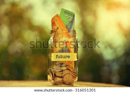 Saving Money Concept With Future Text Written Label On Glass Jar.Selective Focus And Shallow DOF. - stock photo