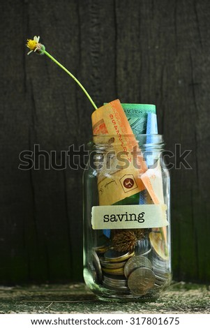 Saving Money Concept With Saving Text Written Label On Glass Jar.Selective Focus And Shallow DOF. - stock photo