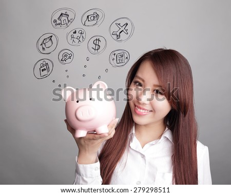 Saving money concept - woman smiling happy and holding pink piggy bank isolated on white background. Asian beauty
