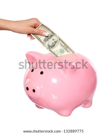 saving money, hand is putting money into piggy bank isolated on white