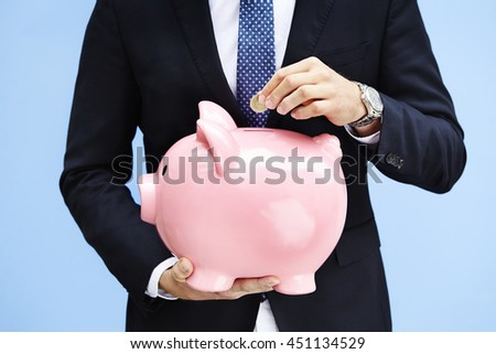 Saving money in piggy bank, close up