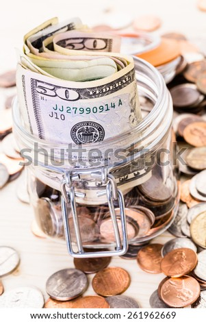 Saving money into glass jar for future investment.