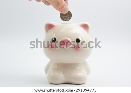 saving money, male hand is putting coin into piggy bank isolated on white