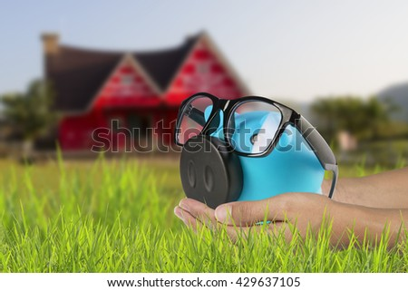 Saving money, Piggy Bank and Coin in Female Hands over Green Grass on abstract blurred background,Saving to buy a house, real estate or home savings, piggy bank in front of property - stock photo
