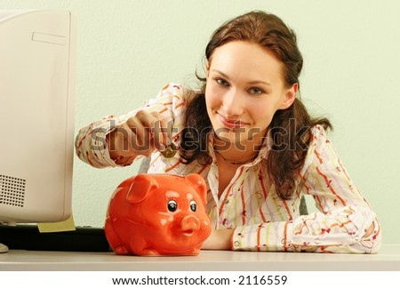 saving money-young woman putting a coin into a red money-box