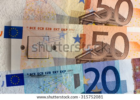 Saving on electricity - Euro banknotes and switch - stock photo