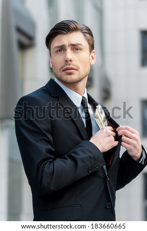 Savings. Businessman Putting money in his Pocket - stock photo