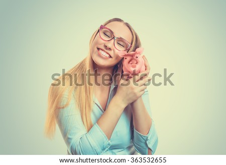 Savings concept. Closeup portrait happy blonde beautiful young business woman bank employee hugging holding piggy bank isolated green background. Positive human emotion facial expression body language - stock photo