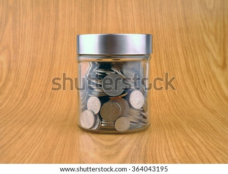 Savings Concept - Glass jar with coins on wooden background.  - stock photo