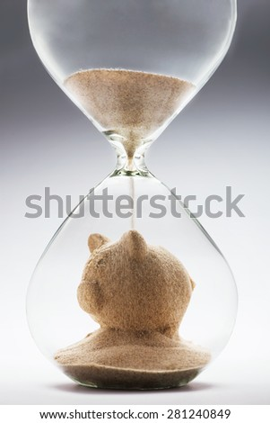 Savings concept with falling sand taking the shape of a piggy bank - stock photo