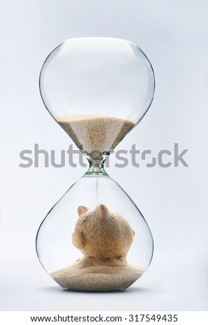 Savings concept with falling sand taking the shape of a piggy bank