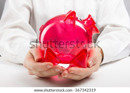 Savings concept. Woman holding piggy coin bank in hands - stock photo