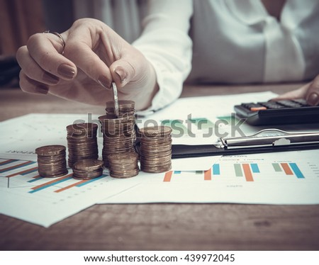 Savings, female hand stacking euro coins into columns above business diagram. toned image - stock photo