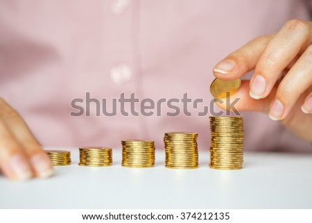 Savings, female hand stacking gold coins into increasing columns