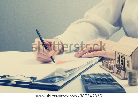 Savings, finances, economy and home budget concept - close up of woman counting at calculator  losses, profit  making notes, working with statistics, analyzing financial results. Toned Image - stock photo